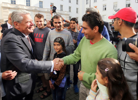 Президент Германии Йоахим Гаук приветствует беженцев
