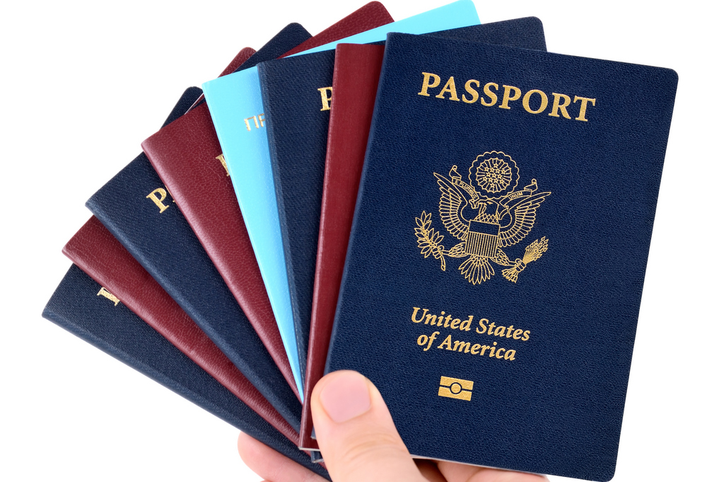 hand holds bunch of passports, USA passport on the front