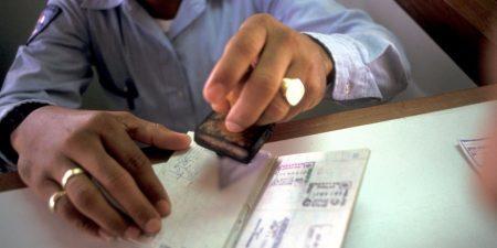 пограничник ставит штамп в паспорт на границе