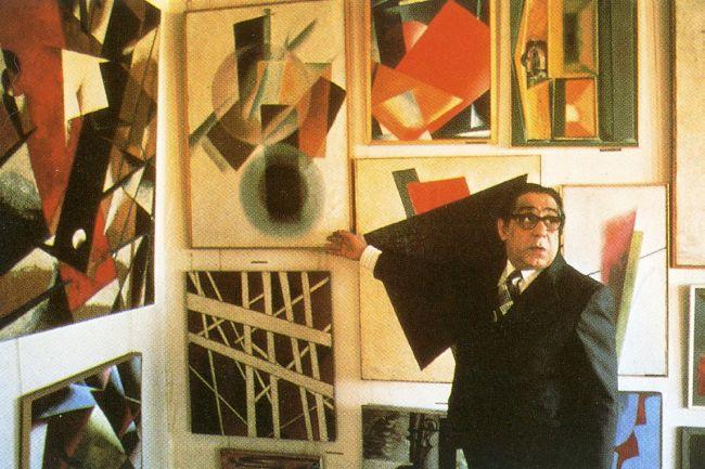 Георгий Костаки на фоне картин из своей коллекции